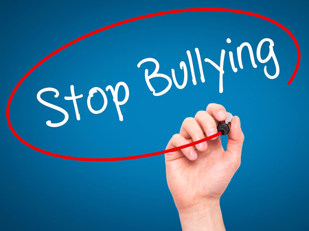 52873356 - man hand writing stop bullying with black marker on visual screen. isolated on blue. business, technology, internet concept. stock photo