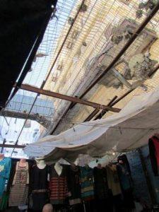Colonos israelies lanzan basura al mercado palestino en Hebrón desde arriba.