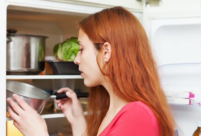 Red-haired woman looking for something in fridge