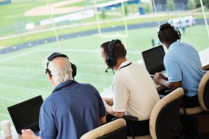 Sportscasters watching and calling a football game in a media press box.