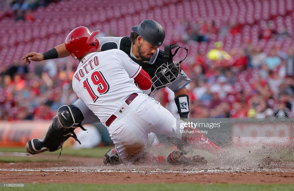 CINCINNATI, OH - APRIL 10: Joey Votto #19 of the Cincinnati Reds slides into the tag of Jorge Alfaro #38 of the Miami Marlins at home plate in the first inning at Great American Ball Park on April10, 2019 in Cincinnati, Ohio. (Photo by Michael Hickey/Getty Images)