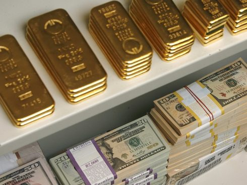 Gold bars and US Dollar bills are pictured in a safe in a bank in Vienna July 21, 2009. REUTERS/Heinz-Peter Bader  (AUSTRIA BUSINESS)