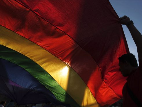 A gay rights activist holds a rainbow flag during a rally to mark the International Day Against Homophobia in Managua May 17,2013. RERUTERS/Oswaldo Rivas (NICARAGUA - Tags: SOCIETY)