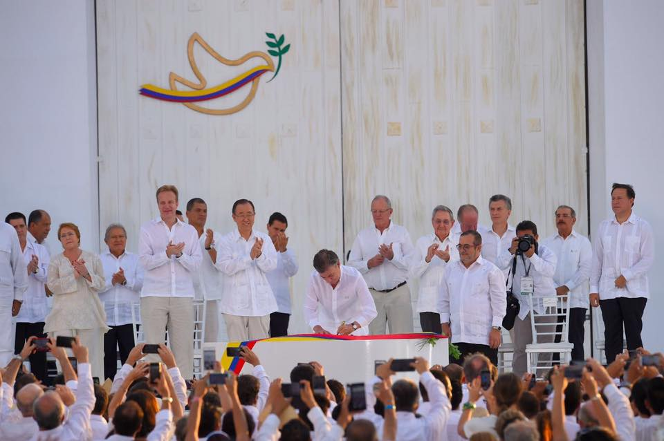 Colombian President Juan Manuel Santos signing the peace deal with Farc leader Timochenko looking on ...