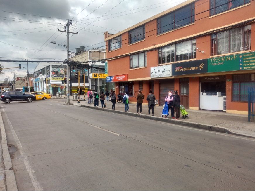 People form a queue, spaced apart in line with recommendations due to coronavirus, to enter a bank in Bogotá, Colombia.