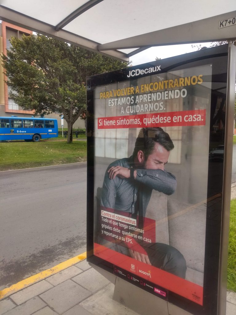 A bus-stop poster warns about Covid-19 symptoms in Bogotá, Colombia.